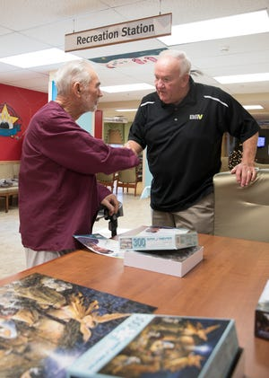 Retired major league umpire Larry Barnett, right, hands out baseball cards and signed pictures to veterans like Ira Wolford at the Chillicothe VA Medical Center on Thursday, December 5, 2019.