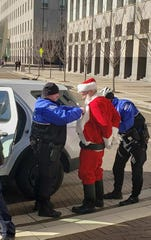 Santa Claus was arrested on the steps of Procter & Gamble's headquarters in Downtown Cincinnati, Thursday, December 5, 2019. Stand.earth accuses P & G's of destroying endangered forests in Canada to make Charmin toilet paper.