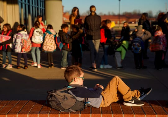 A student relaxes in the afternoon sun while waiting for a bus to depart at Rossview Elementary School in Clarksville on Dec. 4, 2019.