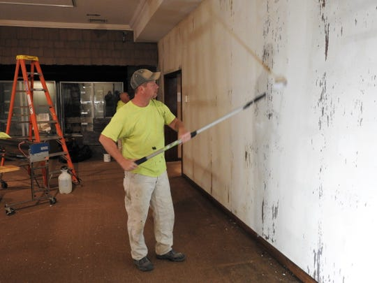 Troy Turner of McKeever Decorating Co. uses a roller on walls at the Johnson-Humrickhouse Museum in the Historic Ohio Room.