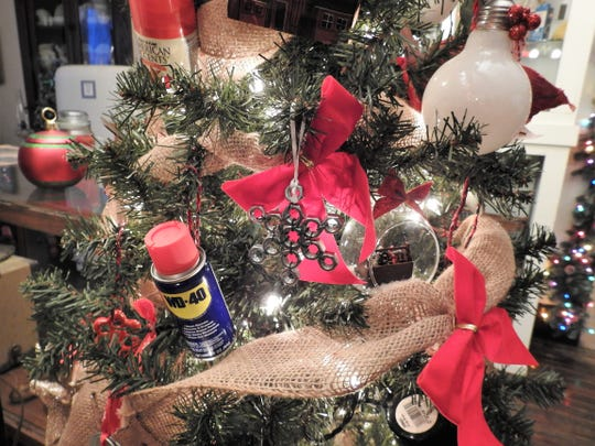 A close up view of a tree donated by Russell's Auto and Hardware for the Warsaw Festival of Trees at the Walhonding Valley Historical Society Museum. It features stars made from lug nuts and small cans of WD-40 among other hardware related items.
