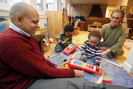 Grinnell College president Raynard Kington, left, with his partner, Peter Daniolos, play with their children, Emerson, 4, and Basil, 1, in their Grinnell home in 2010. Kington is leaving to become the new head of Phillips Academy, Andover.
