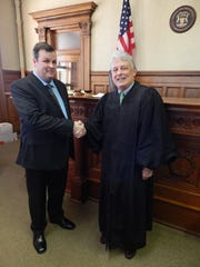 Robert VanSumeren shakes hands with Hillsdale Circuit Judge Michael Smith after being sworn-in as an attorney on Nov. 22. Smith is the same judge who sentenced VanSumeren to prison 20 years ago.