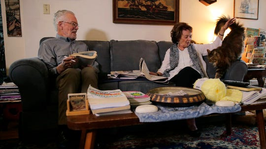 In this Nov. 22, 2019, photo, Charles Flagg, who is stricken with Alzheimer's disease, works on a word puzzle while sitting with his wife Cynthia, right, at their home in Jamestown, R.I. Flagg is participating in a study on the drug Aducanumab.