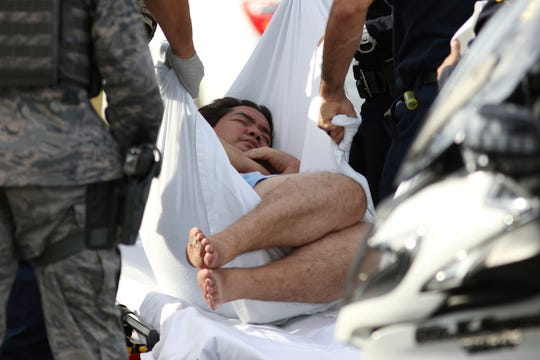 An unidentified male is taken away by officers outside the main gate at Joint Base Pearl Harbor-Hickam, Wednesday, Dec. 4, 2019, in Hawaii, following a shooting.