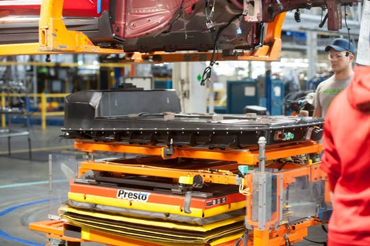 A battery is lifted into the chassis of a Chevrolet Bolt EV at the General Motors assembly plant in Lake Orion.
