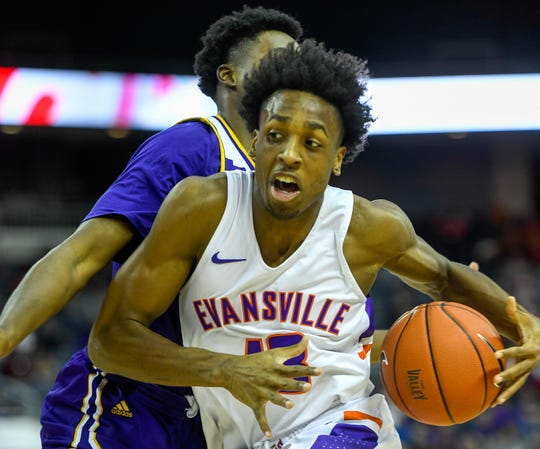 Evansville's DeAndre Williams (13) drives past defense from Western Illinois' James Claar (24) as the Western Illinois Leathernecks play the Evansville Purple Aces Wednesday evening at the Ford Center, December 4, 2019.