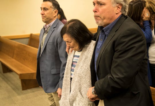 Mary Ann Groves the mother of Teresa Sievers is surrounded by her sons Frank Longobardi, left, and Patrick Tottenham as they react to a guilty verdict in the trial of Mark Sievers on Wednesday Dec, 4, 2019. .