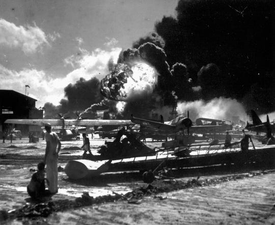In this Dec. 7, 1941 photo provided by the U.S. Navy, sailors stand among wrecked airplanes at Ford Island Naval Air Station as they watch the explosion of the USS Shaw, background, during the Japanese surprise attack on Pearl Harbor, Hawaii. More than 2,300 U.S. service members and civilians were killed in the strike which brought the United States into World War II. (U.S. Navy via AP)