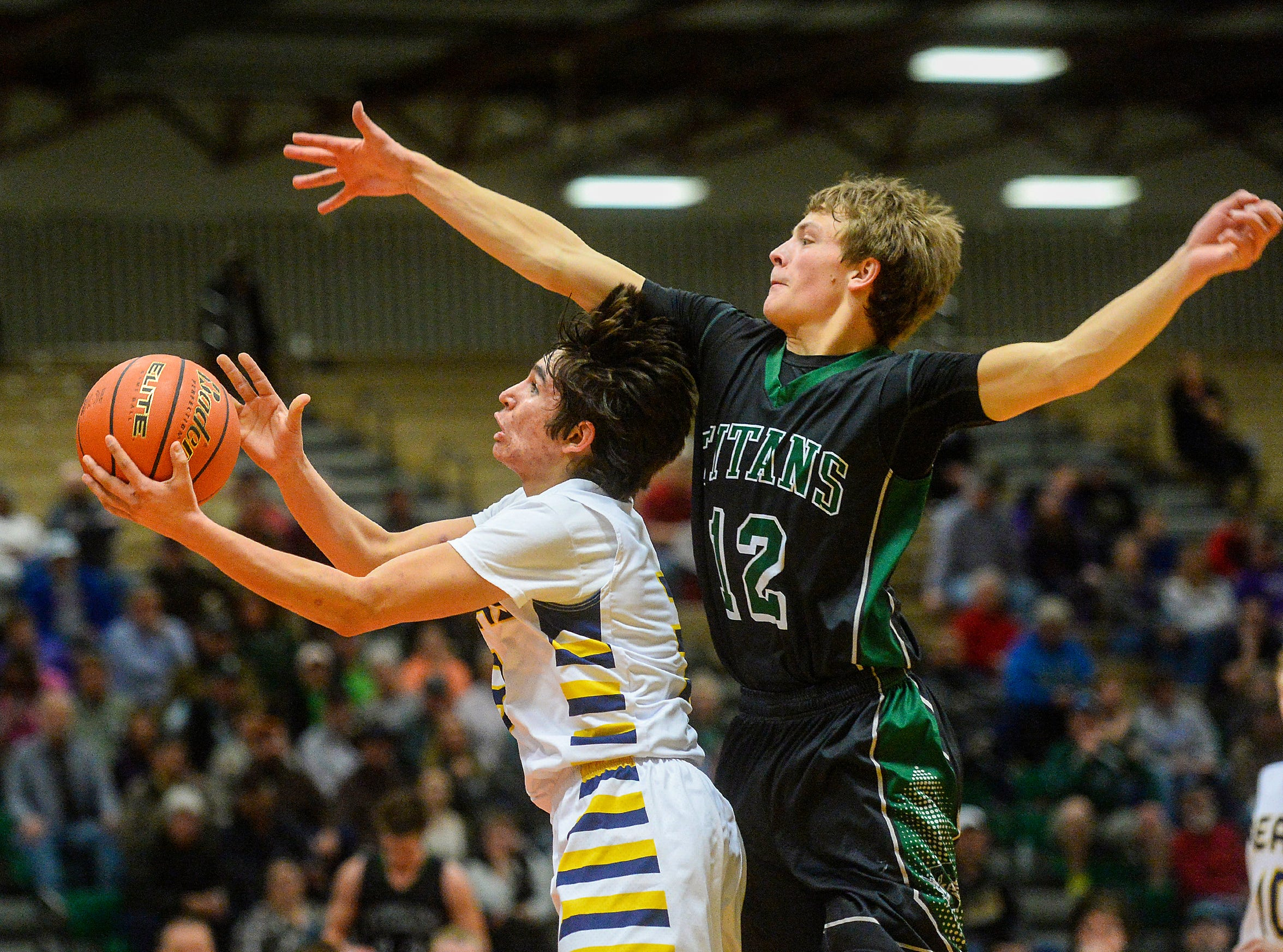 Box Elder's Brandon The Boy goes in for a layup as Tri-City's Chance McAllister defends during the Northern C Divisional Tournament in the Four Seasons Arena, Wednesday.