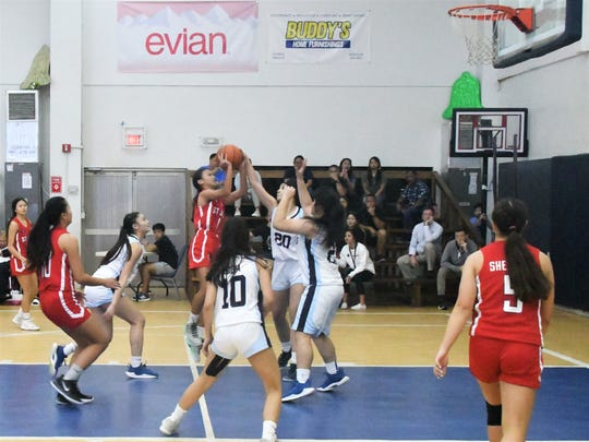 St. John's No. 1 Michelle Sule gets her shot blocked by Saint Paul's No. 20 Monica Giger in their IIAAG High School Girls Basketball game Dec. 4 at Saint Paul. The Warriors defeated the Knights 43-41 in overtime.