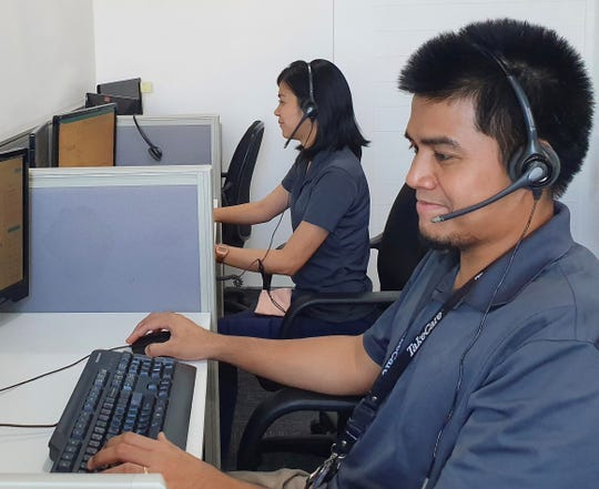 Lea Hernaez, utilization management team lead, and Jimmy Azarcon, medical review specialist, assist members calling TakeCare's medical referral office in the Philippines.