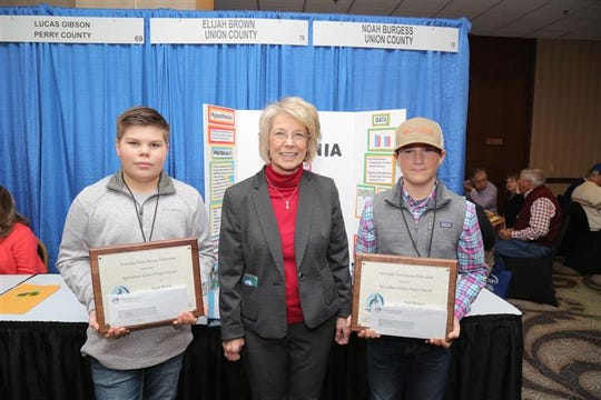 Vicki Bryant of the Kentucky Farm Bureau State Women's Committee presents Elijah Brown and Noah Burgess an award of recognition for their participation in the 2019 Science in Agriculture program.