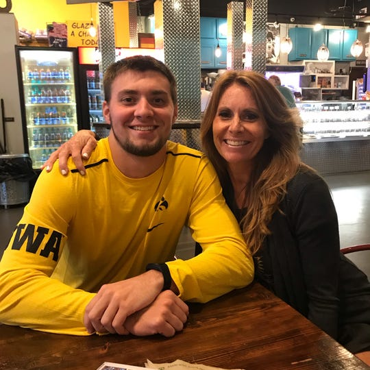 Iowa kicker Keith Duncan is shown at a donut shop with his mother, Jennifer. His mom and dad travel 978 miles from Weddington, North Carolina, to home games at Kinnick Stadium.