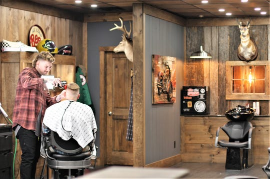 Barber Matt Parton cuts his client's hair at the new 33 Barbershop in Halls. It is a close-knit family: Parton dates owner Bobby Brown's other daughter, and manager and master barber Brian Morgan dates Courtney Brown, owner of the Salon Odara next door.