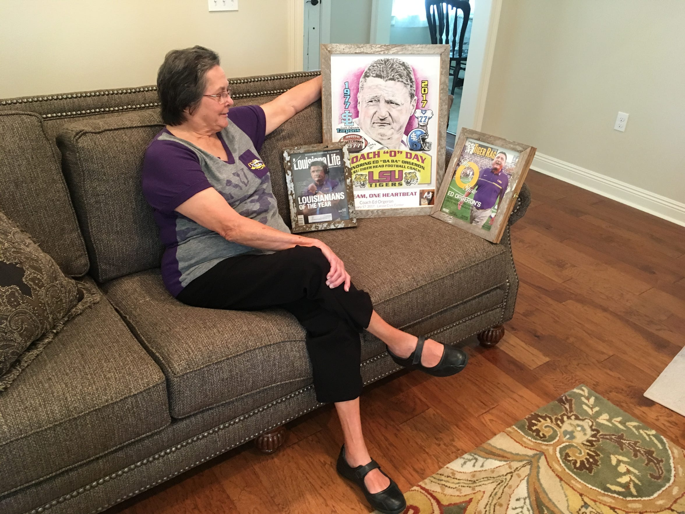 "In this Aug. 22, 2017 photo, Cornelia ""Coco"" Orgeron, shows off memorabilia marking the ascension of her son, Ed Orgeron, to head coach at LSU, at her home in Larose, La."