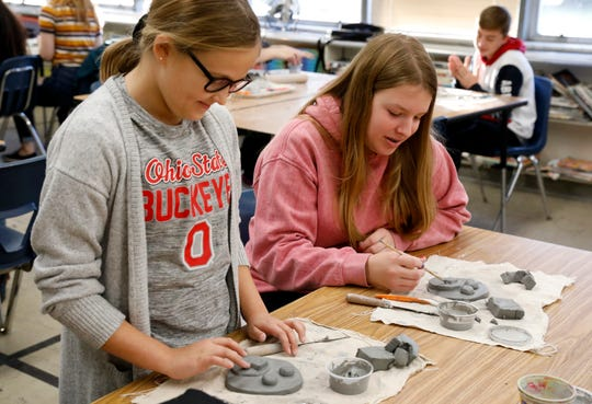 Jaidyn Green, left, and Kaitlyn Campbell work on clay portraits of dogs from the Fairfield Area Humane Society Wednesday afternoon, Dec. 5, 2019, at General Sherman High School in Lancaster. Seventh graders in Karla Young's art classes are making the portraits based off of pictures of animals from the humane society's website.