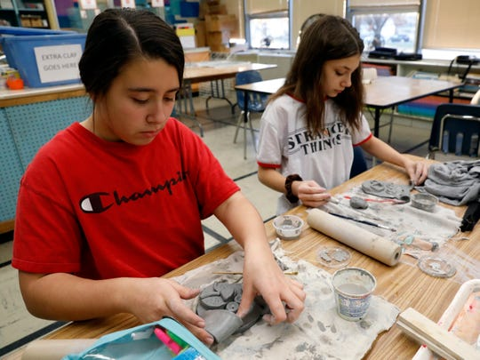 Addie Dilley, left, and Riley Bubeck work on clay portraits of dogs from the Fairfield Area Humane Society Wednesday afternoon, Dec. 5, 2019, at General Sherman High School in Lancaster. Seventh graders in Karla Young's art classes are making the portraits based off of pictures of animals from the humane society's website.
