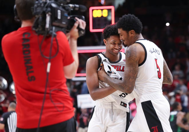 An ACC video crew shoots U of L's David Johnson (13) and teammate Malik Williams (5), right, celebrating after they defeated USC Upstate at the Yum Center in Louisville, Ky. on Nov. 20, 2019.