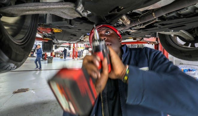 David Horton puts a shield back on the bottom of a car after an oil change at Oxmoor Ford.  Horton is a student at Breckinridge Metro High School and has gotten his internship opportunity through a program at the school.