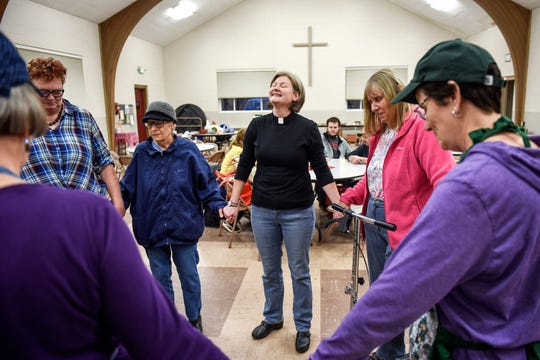 The Rev. Linda Stephan, center, leads a group of patrons and volunteers in prayer during the Open Table free community meal on Wednesday, Dec. 4, 2019, at the Williamston United Methodist Church. The meal is served every Wednesday from 5 to 6 p.m. and anyone can attend.