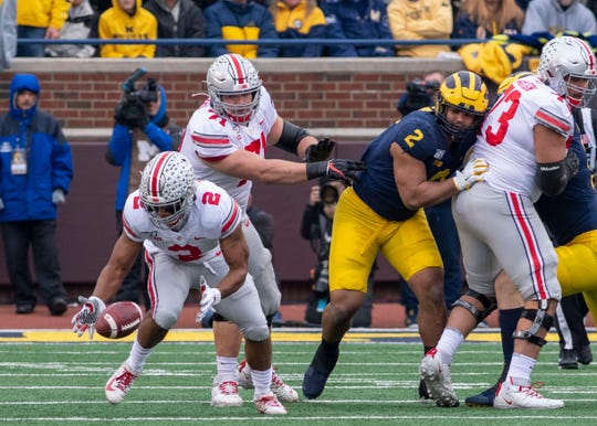 Ohio State running back J.K. Dobbins scoops up his own fumble and darts 41 yards to set up a touchdown in the Buckeyes' 56-27 rout of Michigan