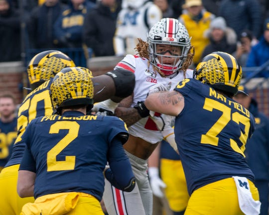 Ohio State defensive end Chase Young draws a crowd as he tries to get to the  quarterback last Saturday at Michigan