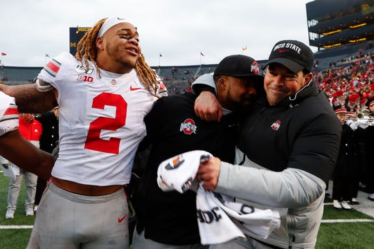 Ohio State head coach Ryan Day celebrates the 56-27 win at Michigan with assistant coach Al Washington Jr. and defensive end Chase Young