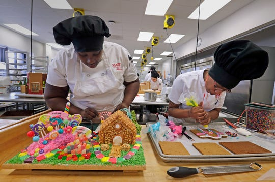 From left Marquita Walker and Malisha Davis work on a Gingerbread house based on the board game Candyland.