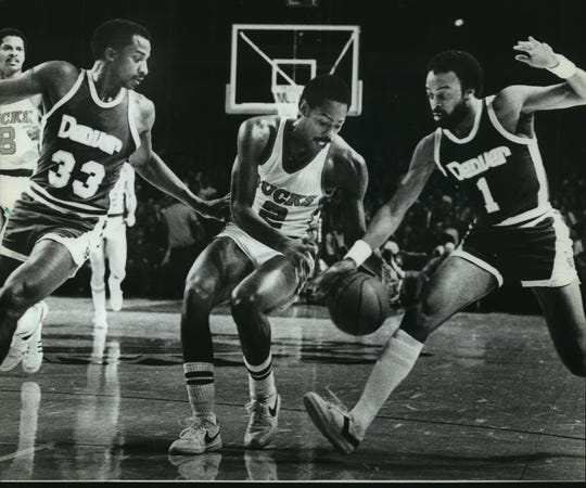 David Thompson (33) and Ken Higgs (1) of the Denver Nuggets battled Milwaukee's Junior Bridgeman for possession of the basketball during a game in 1982.