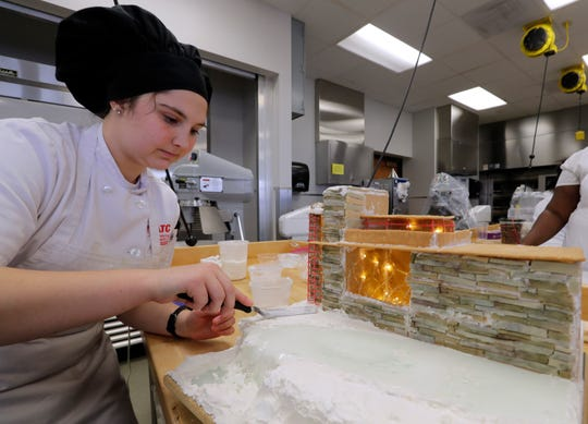Isabelle DeBlaey works on her Frank Lloyd Wright house using fondant icing and isomalt, a crystal ingredient.