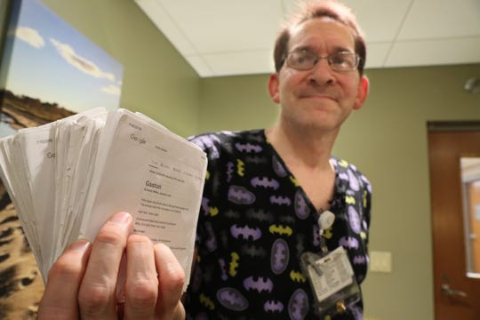 John Melara shows the stack of printed song lyrics that he carries in his pocket as he wheels patients to and from their medical imaging appointments at Aurora West Allis Medical Center.