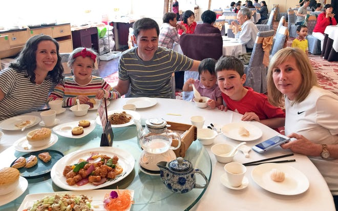 From left, Alison Sherwood, daughter Mara, 6, husband Peter, new daughter Lydia, 2, son Corban, 8, and Alison's mother, Diane Fonte, enjoy a restaurant meal together in China.