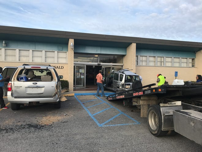 A bus crashed into a parked car, which pushed the vehicle into the front of the Carver-McDonald Branch Library in Monroe on Thursday.