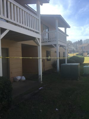 Crime scene tape surrounds an apartment unit with a shattered glass door the day after two men were fatally shot at the Birchwood Apartments complex.