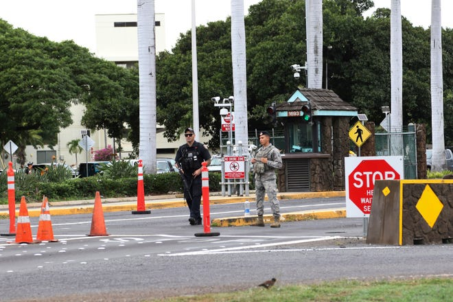 Security stand outside the main gate at Joint Base Pearl Harbor-Hickam, Wednesday, Dec. 4, 2019, in Hawaii.