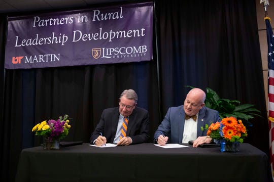 Lipscomb University President L. Randolph Lowry III, left, and UT Martin Chancellor Keith Carver, right, sign an agreement for a new partnership to create a rural education program.