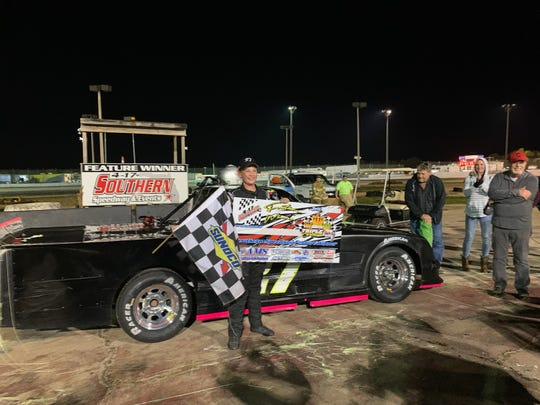 Cody Krucker poses with the checkered flag and first-place banner he got by winning the pro trucks championship race at 4-17 Southern Speedway in Punta Gorda on Nov. 30, 2019. It was the first career win for Krucker, a 14-year-old freshman at Estero High School, and it earned him the season points title at 4-17.