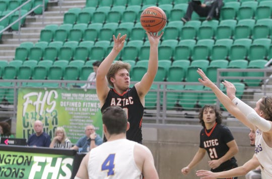 Aztec's Mikey Phillips knocks down a long 2-pointer against San Juan during the Marv Sanders Invitational boys basketball tournament Thursday at Scorpion Arena in Farmington.