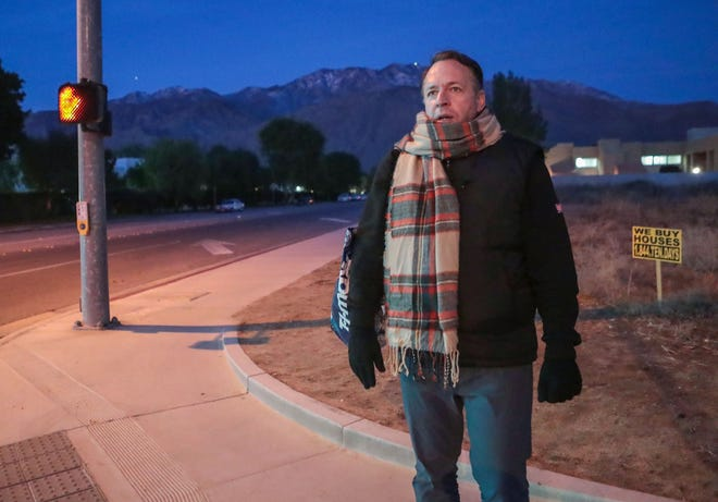 Just before dawn, Philven Sitton waits for the bus after sleeping in a temporary homeless shelter in Palm Springs, December 2, 2019.