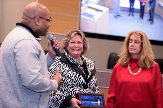 Indio Councilman Waymond Fermon thanks outgoing Mayor Lupe Ramos Amith, center, for her service as Mayor Pro Tem Elaine Holmes, right, listens inside Indio City Hall in Indio, Calif., on Wednesday, December 4, 2019.