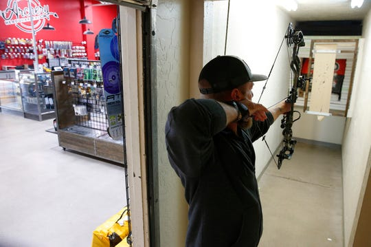 Bow technician Travis Browning tests a bow while tuning it at Archery Headquarters in Chandler on Nov. 26, 2019. The specialty store has been open for 30 years.