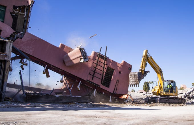 Workers tear down parts of Papago Plaza on Dec. 5, 2019, in Scottsdale.  The shopping center, Scottsdale's oldest, is being replaced with a contemporary mixed-use development.
