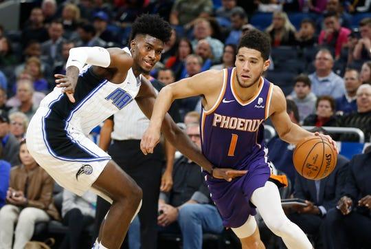Dec 4, 2019; Orlando, FL, USA; Phoenix Suns guard Devin Booker (1) drives past Orlando Magic forward Jonathan Isaac (left) during the first quarter at Amway Center. Mandatory Credit: Reinhold Matay-USA TODAY Sports