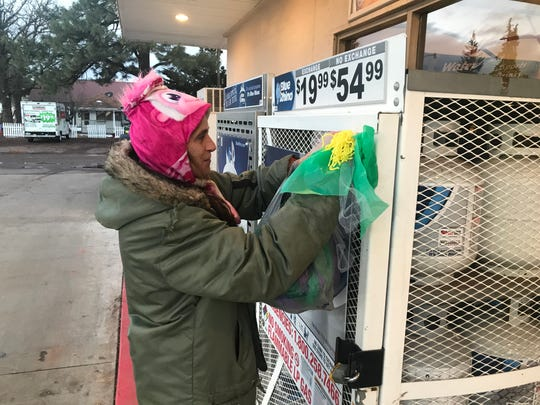 Mary Holling puts up a green and gold ribbon at a Lakeside gas station on Dec. 4, 2019 to show her support for the Rawlings family after two children were killed in a fatal creek crossing. Willa Rawlings, 6, remains missing.