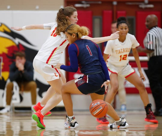 Perry's Tatyanna Clayburne (1) dribbles behind her back against Chaparral's Jess Finney (10) during the 7th Annual Hoophall West in Scottsdale December 4, 2019.