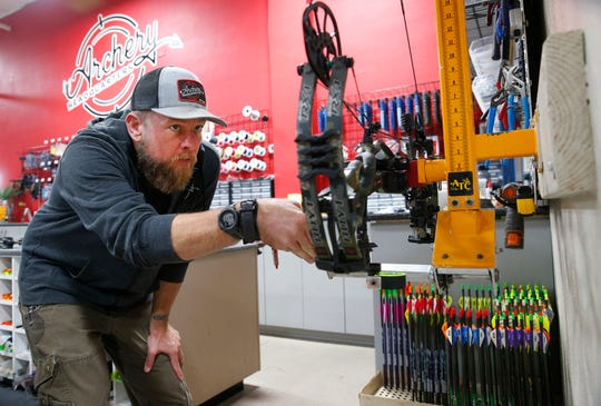 Bow technician Travis Browning tunes a bow at Archery Headquarters in Chandler on Nov. 26, 2019. The specialty store has been open for 30 years.
