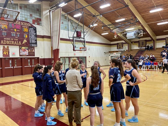The Ursuline girls basketball team huddles during a timeout on Wednesday as it visited Arlington High School.