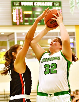 York College's Molly Day aims for the hoop while Lancaster Bible College's Christine Graves defends during womens' basketball action at Grumbacher Sport and Fitness Center at York College of Pennsylvania in Spring Garden Township, Wednesday, Dec. 4, 2019. York College would win the game 77-52. Dawn J. Sagert photo