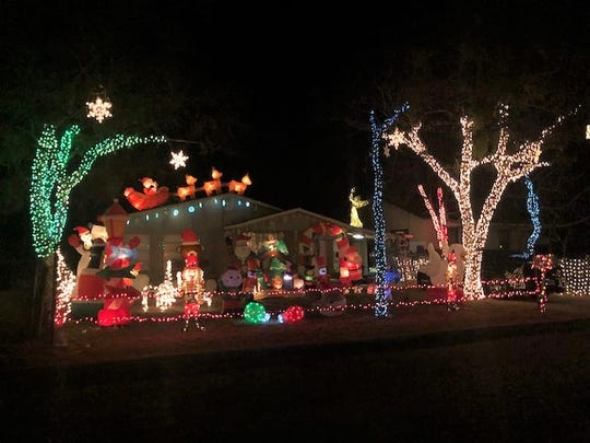 Holiday lights displayed at 2710 Abilene St. with Santa and his reindeer on the roof.